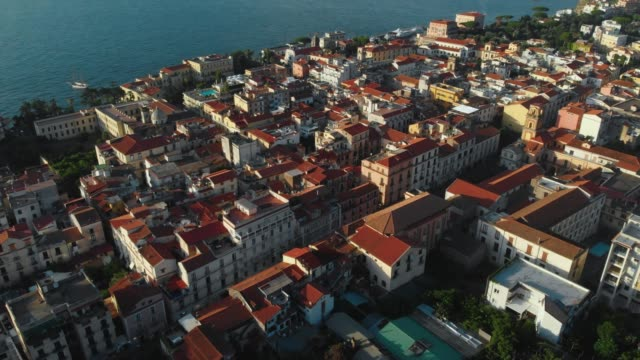 beautiful panoramic aerial view on the center of sorrento city, sunset, houses and streets, sea views and a vizuvius, napoli in the distance. travel and vacation concept on italy. infrastructure. - ナポリ点の映像素材/bロール