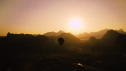 Beautiful Panoramic Nature Landscape of Countryside Mountains in Vang Vieng, Laos. The Cloudless Sunset in the Distance While a Hot Air Balloon Floats Along