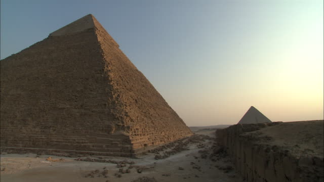 a beautiful pastel sky glows beyond pyramids in giza, egypt. - rubble stock videos & royalty-free footage