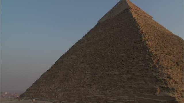 vidéos et rushes de a beautiful pastel sky glows beyond pyramids in giza, egypt. - lieu de culte