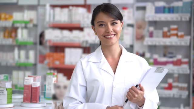 beautiful pharmacist at a drugstore looking at the camera smiling - pharmacy stock videos & royalty-free footage