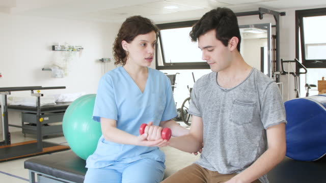 beautiful physical therapist helping male patient doing exercises with free weights - physical therapist stock videos & royalty-free footage