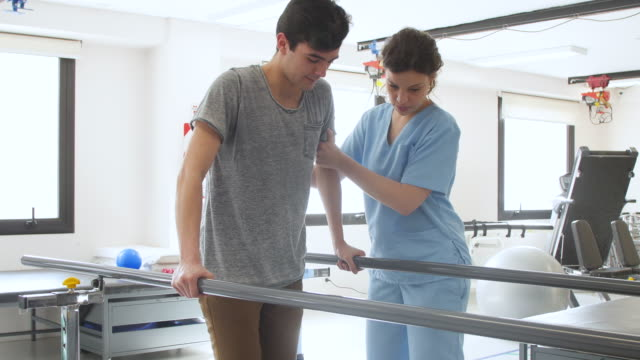 beautiful physical therapist helping male patient walk while leaning on parallel bars both looking happy - physical therapy stock videos & royalty-free footage