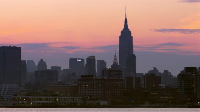 vídeos de stock, filmes e b-roll de beautiful pink and orange sky above new york city skyline along the hudson river. - prédio empire state