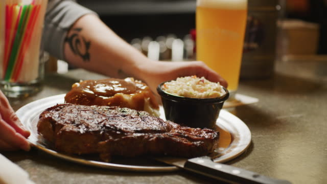 beautiful plate with huge grilled steak, cole slaw and mashed potatoes and gravy is served at a bar restaurant. - coleslaw stock videos & royalty-free footage