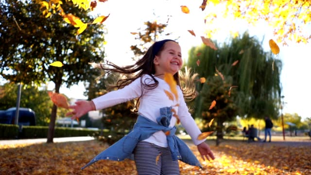 beautiful playful girl throwing leaves in autumn - serene people stock videos & royalty-free footage