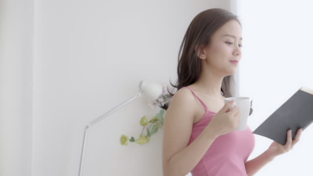 Beautiful portrait young asian woman relax and leisure standing learning with reading book and drink coffee for exam at home, girl is student knowledge with study education and lifestyle concept, slow motion.