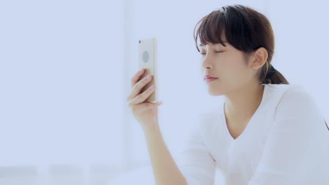 bellissimo ritratto giovane donna asiatica seduta a scattare un selfie con smartphone in camera da letto al mattino a casa, ragazza sta fotografando con felice e sorriso con divertimento, concetto di stile di vita. - creazione video stock e b–roll