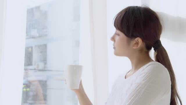 Beautiful portrait young asian woman smile and drink a cup of coffee with relax in the morning at window, girl happy with leisure breakfast is beverage for fresh, lifestyle concept.