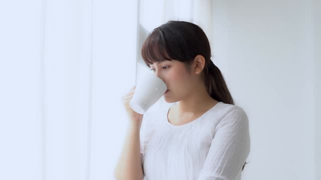 Beautiful portrait young asian woman smile and drink a cup of coffee with relax in the morning at window, girl happy with leisure breakfast is beverage for fresh, lifestyle concept, slow motion.