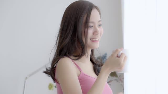 美しい肖像画若いアジアの女性の笑顔と窓で朝にリラックスしてコーヒーを飲みます, レジャーで幸せな女の子は、新鮮なライフスタイルのコンセプト、スローモーションのための飲料です� - 少女点の映像素材/bロール