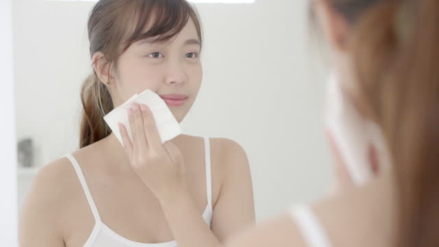 Beautiful portrait young asian woman smile and joy with skin care use oil blotting paper on face looking mirror in the bathroom, beauty asia girl happy and cheer makeup and cosmetic, health care on facial concept.