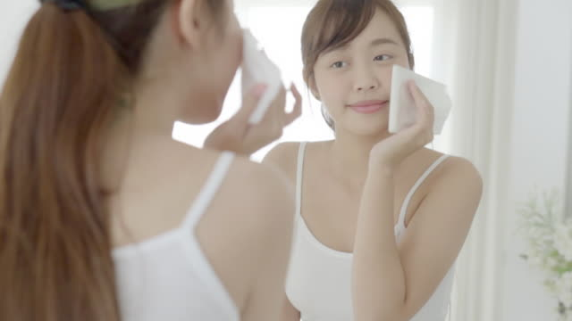 beautiful portrait young asian woman smile and joy with skin care use oil blotting paper on face looking mirror in the bathroom, beauty asia girl happy and cheer makeup and cosmetic, health care on facial concept. - body care stock videos & royalty-free footage