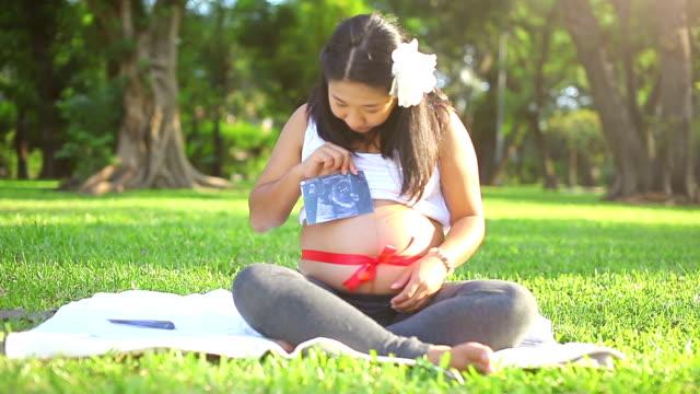 vídeos y material grabado en eventos de stock de hermosa mujer embarazada asiática relajante en el parque con cinta roja - escarapela