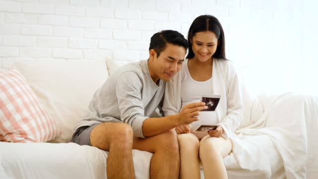 beautiful pregnant woman and her husband are holding ultrasound scan on her belly in sofa at home, pregnant and family concept - ultrasound stock videos and b-roll footage