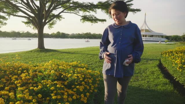 beautiful pregnant woman enjoying spring. - maternity wear stock videos & royalty-free footage
