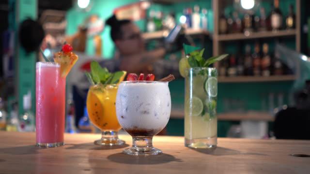 vídeos de stock, filmes e b-roll de cocktailpreparados bonitos no contador e no bar de barras que preparam outro no fundo - barman