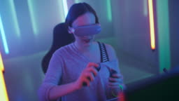 Beautiful  Pro Gamer Girl Wearing Virtual Reality Headset Plays in Online Video Game, Gesturing Using Controllers. Cool Retro Neon Colors in the Room.