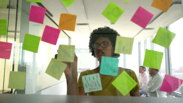 beautiful professional black woman planning a business strategy with adhesive notes on window looking very happy - adhesive note stock videos & royalty-free footage