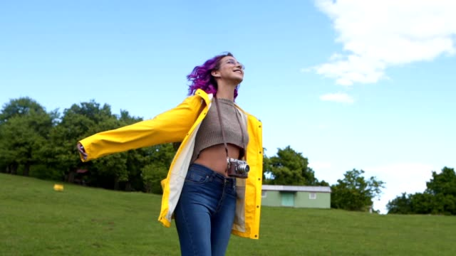 beautiful purple haired girl enjoying the day outdoors - raincoat stock videos & royalty-free footage