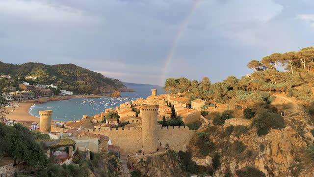 vidéos et rushes de beautiful rainbow after the rain in the iconic tossa de mar in the catalan costa brava coast. vista de un espectacular arco iris con el pueblo amurallado de tossa de mar. - mar