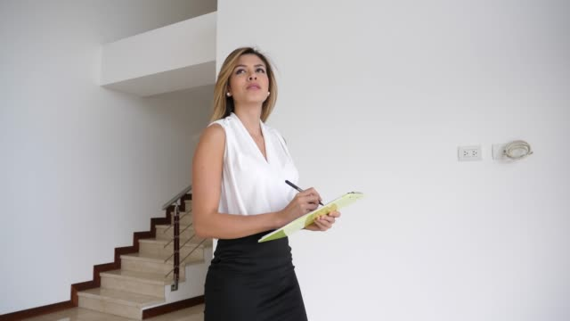 beautiful real estate agent checking the property and writing down everything on a document on clipboard - real estate stock videos & royalty-free footage
