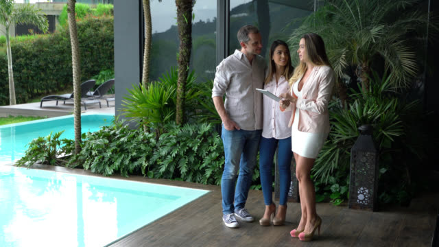 Beautiful real estate agent with tablet showing a property to happy couple looking at the pool and outside area of house