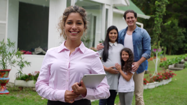 beautiful realtor facing camera smiling holding a tablet and family at background - insurance agent stock videos & royalty-free footage