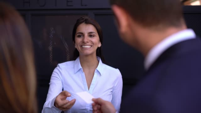 vídeos de stock e filmes b-roll de beautiful receptionist at the hotel handing key to business couple checking in - hotel