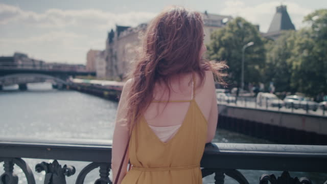 beautiful red haired woman standing on bridge over spree river in berlin, germany, enjoying sunshine, smiling, looking happy - sonnenhut stock-videos und b-roll-filmmaterial