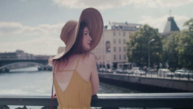 beautiful red haired woman with large sun hat standing on bridge over spree river in berlin, germany, enjoying sunshine, smiling, looking happy - straw hat stock videos and b-roll footage