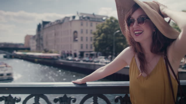 Beautiful red haired woman with large sun hat standing on bridge over Spree river in Berlin, Germany, waving at boats, enjoying the sunshine, looking happy