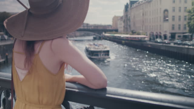 beautiful red haired woman with large sun hat standing on bridge over spree river in berlin, germany, waving at boats, enjoying the sunshine, looking happy - sun hat stock videos & royalty-free footage