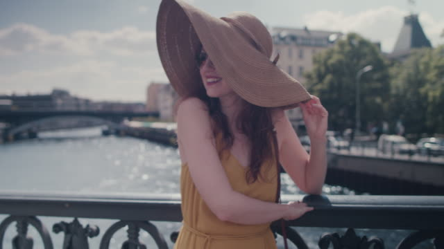 Beautiful red haired woman with large sun hat standing on bridge over Spree river, smiling, looking happy, enjoying the sun