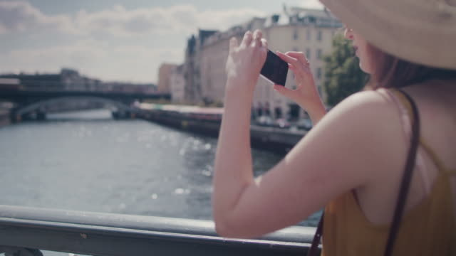 beautiful red haired woman with large sun hat standing on bridge over spree river in berlin, germany, taking photos with cell phone - tourist stock videos & royalty-free footage
