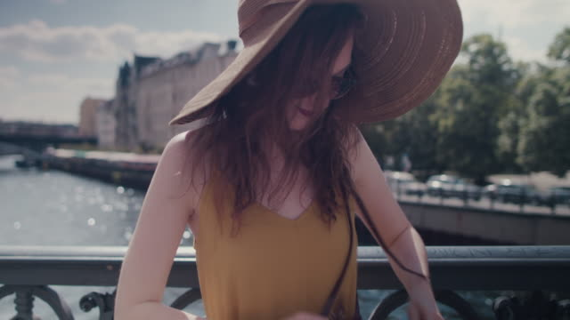 beautiful red haired woman with large sun hat standing on bridge over spree river in berlin, germany, taking photos with cell phone - purse stock videos & royalty-free footage