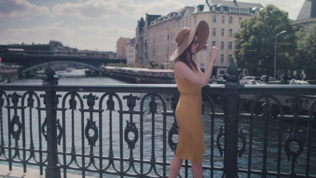 Beautiful red haired woman with large sun hat standing on bridge over Spree river in Berlin, Germany, taking photos with cell phone