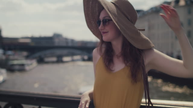 beautiful red haired woman with large sun hat standing on bridge over spree river, smiling, holding cell phone, enjoying sun - sun hat stock videos & royalty-free footage