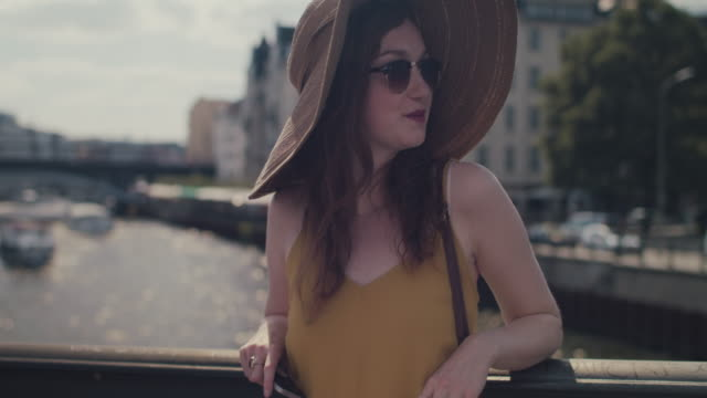 vídeos de stock e filmes b-roll de beautiful red haired woman with large sun hat standing on bridge over spree river in berlin, germany, looking at cell phone, enjoying sun - chapéu de palha