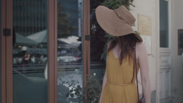 beautiful red haired woman with large sun hat waiting outside of cafe in front of large windows in berlin, germany. - part of a series stock videos & royalty-free footage