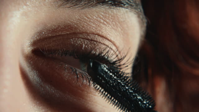 beautiful red haired young woman applying mascara eye makeup - extreme close up stock videos & royalty-free footage