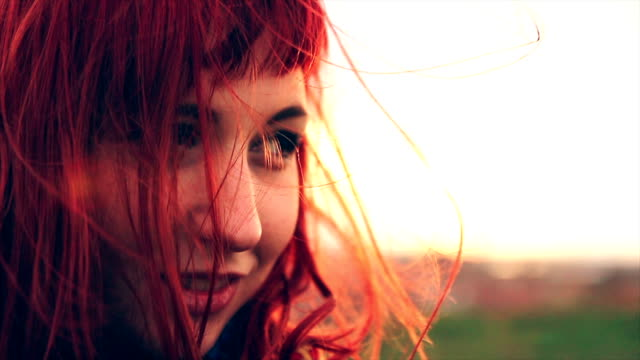 Beautiful red haired young woman enjoying windy spring day on hill upper the town