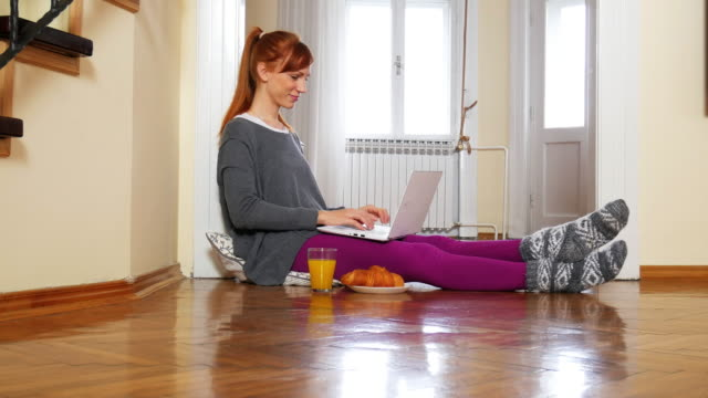 Beautiful red head woman at home, using internet for her online business