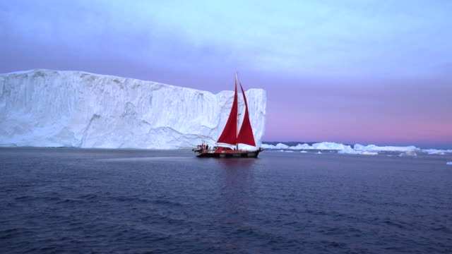 beautiful red sailboat near large mass of ice - disko bay, greenland - inlet stock videos & royalty-free footage