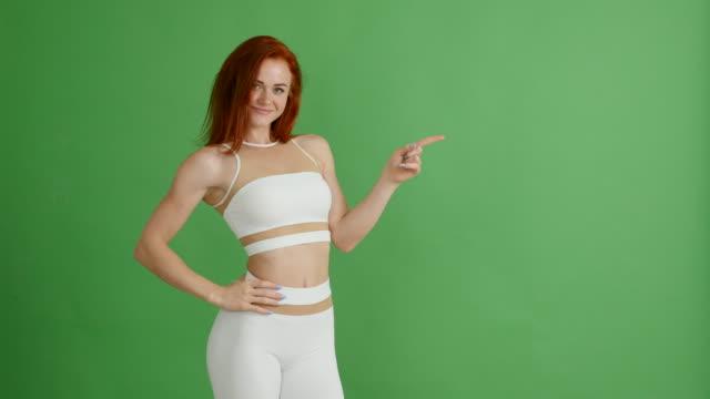 Schöne rothaarige Frau im Sport einheitliche zeigt textfreiraum auf grünem Hintergrund, Chroma-Key