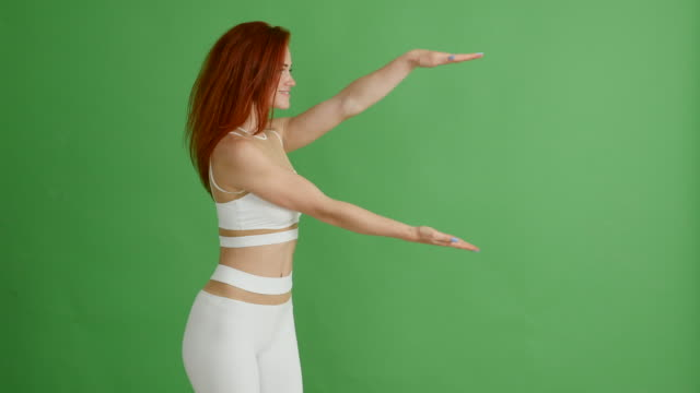 Beautiful red-haired woman in sports uniform shows copy space on green background, Chroma Key