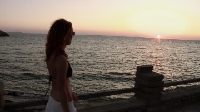 WS TS beautiful redhaired woman walks on mediterranean esplanade at sunset / Putzu Idu, Sardinia, Italy