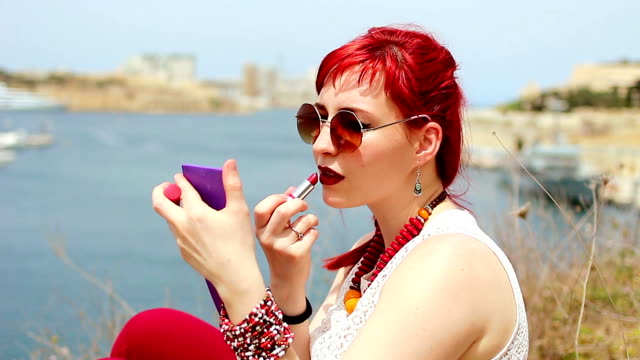 Beautiful redhead girl applying lipstick over her lips by the sea