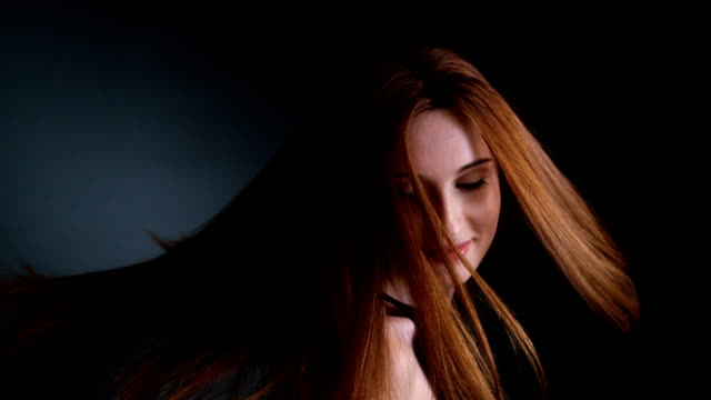 Beautiful redhead girl flipping her long hair