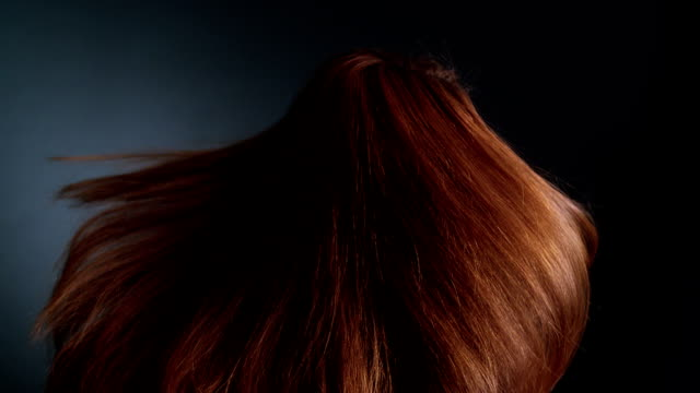 Beautiful redhead girl rotating. Her long hair waves